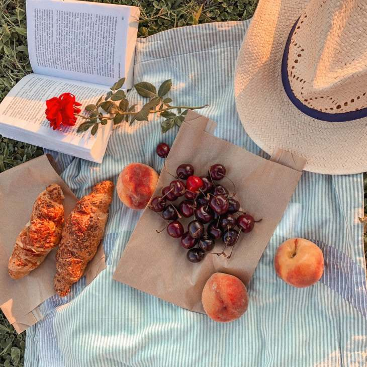 A picnic flatlay filled with a book, hat, croissants, peaches, cherries on brown paper bags on a picnic blanket.