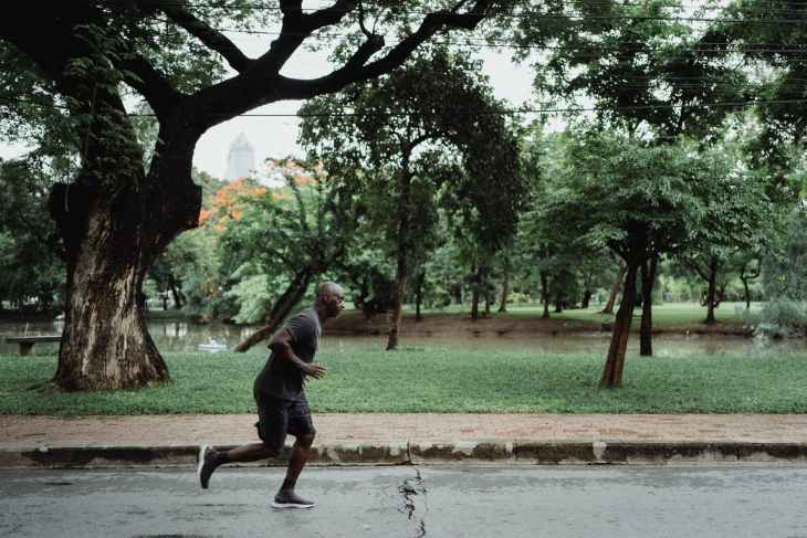 A man running in the street with trees in the background.