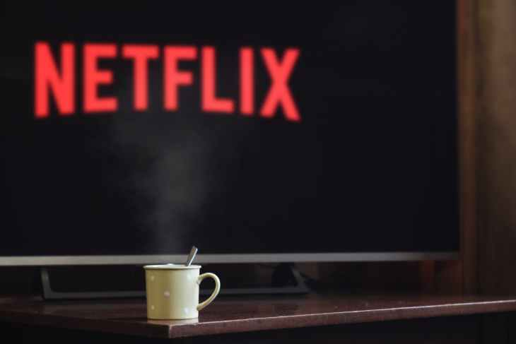 A TV with Netflix on it and a cup of drink in front of it.