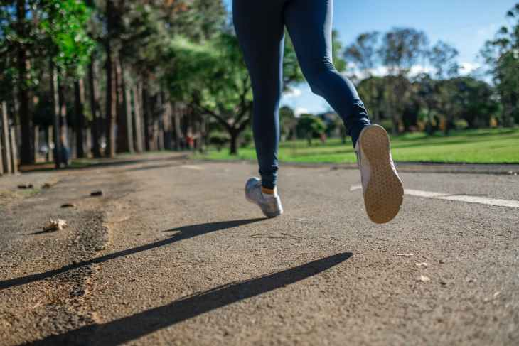 A picture of some legs running on the road in a park with trees and grass in the background.
