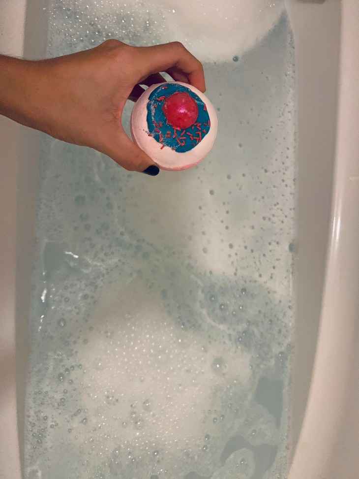 A hand holding a bath bomb over a bath tub filled with water.