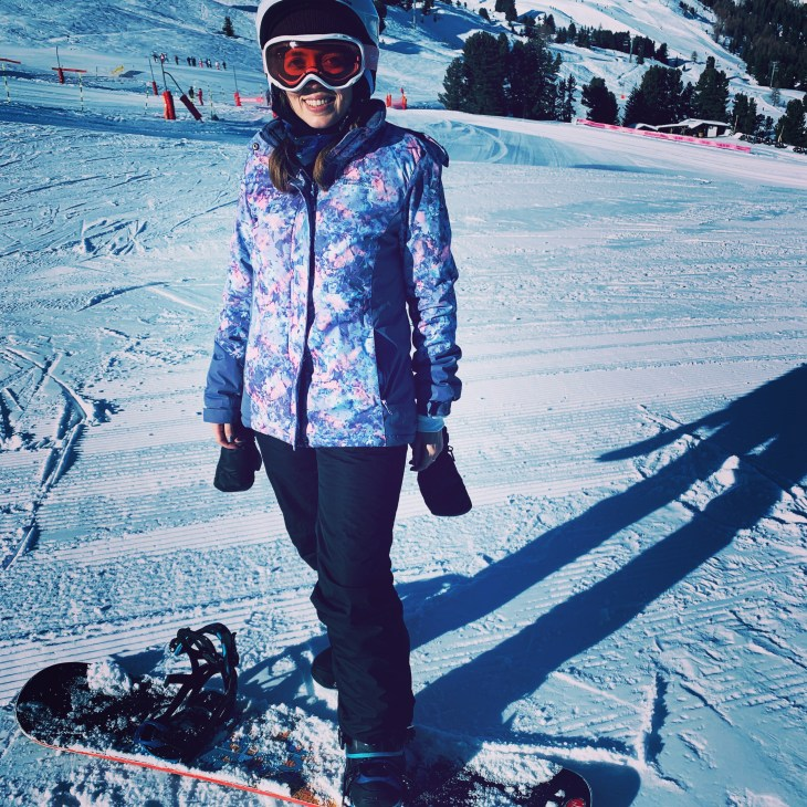 A woman in ski gear smiling whilst one foot strapped into a snow board on a mountain.