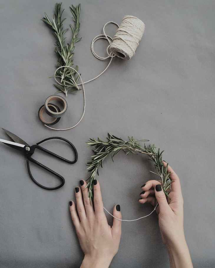 Tree branches, tap and string and a pair of scissors and a hand holding the tree branches together to make a wreath.