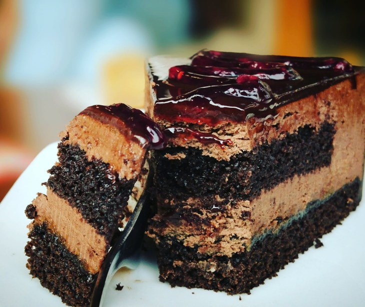A chocolate three layered cake with jam on the top on a plate