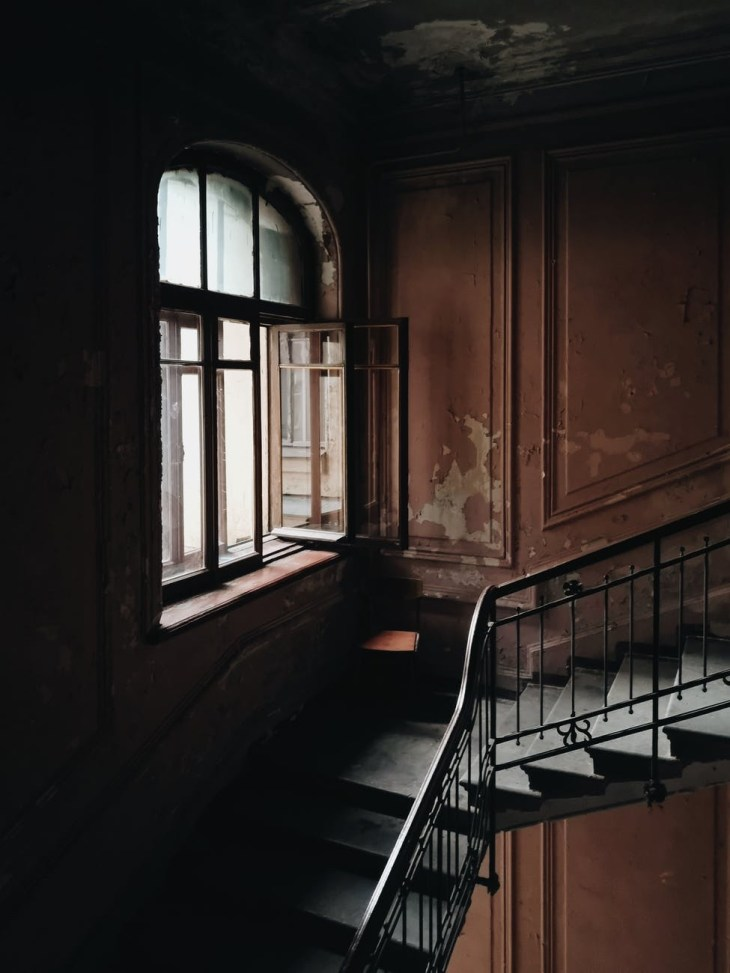 A view of a staircase and a huge open window in the middle