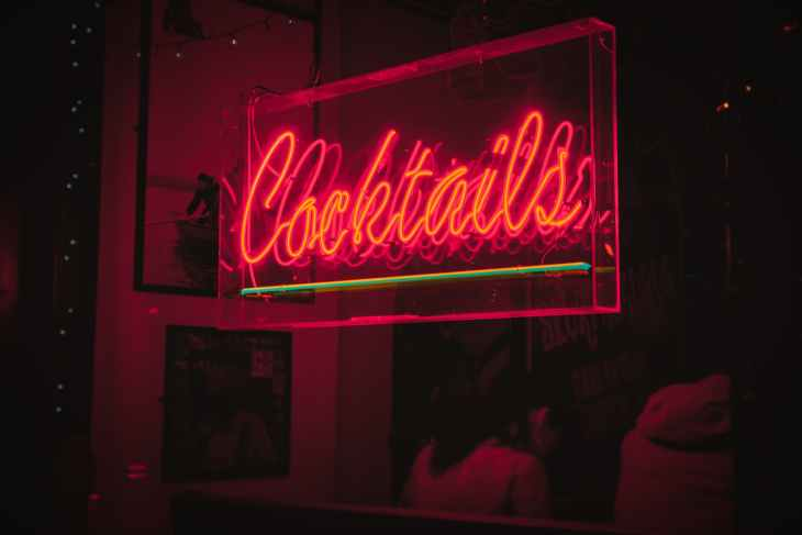 """A sign from a bar that says """"cocktails"""" and is lit up in a dark pink colour."""