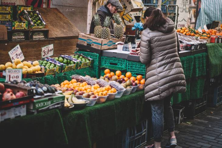 A woman standing looking at fruit and veg at a market stool.