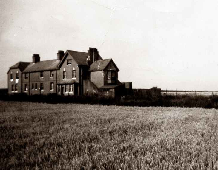 An old black and white photo of a huge house in the middle of a field.