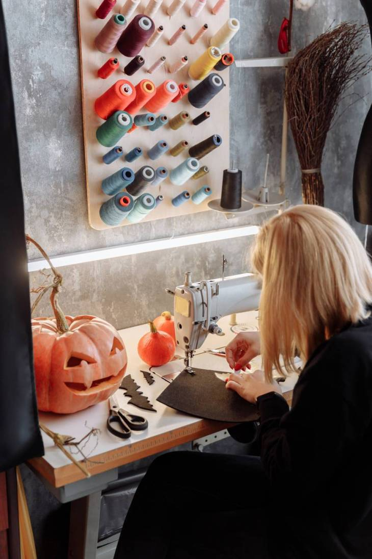 A woman using a sewing machine to create Halloween crafts on black felt. With a huge orange pumpkin