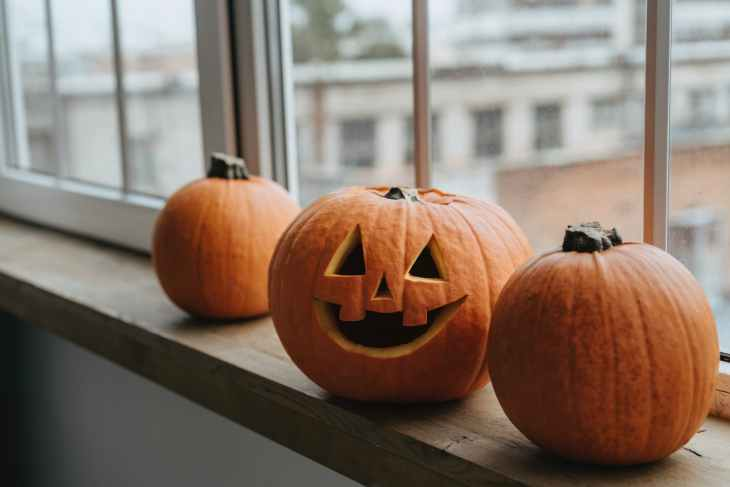 Three pumpkins on a windowsill, the huge one in the middle is carved with a smiley face.