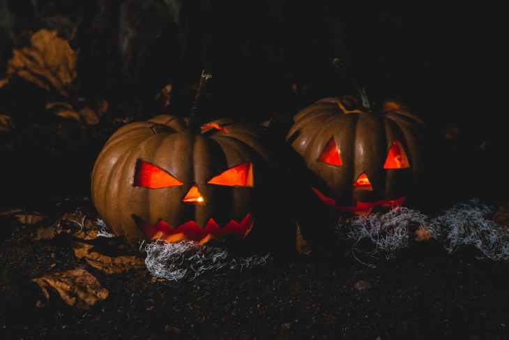 Two pumpkins that are both lit up in the dark on the ground in the mud.
