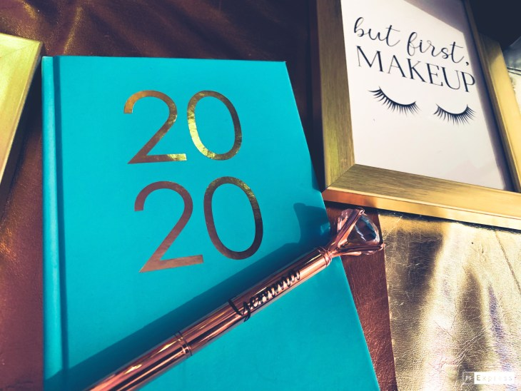 "A blue diary with gold ""2020"" on it and a rose gold pen with my name ""Gemma"" on it that has a diamond on the end. Next to a photo frame with ""but first make up and some eyelashes"" in the frame."