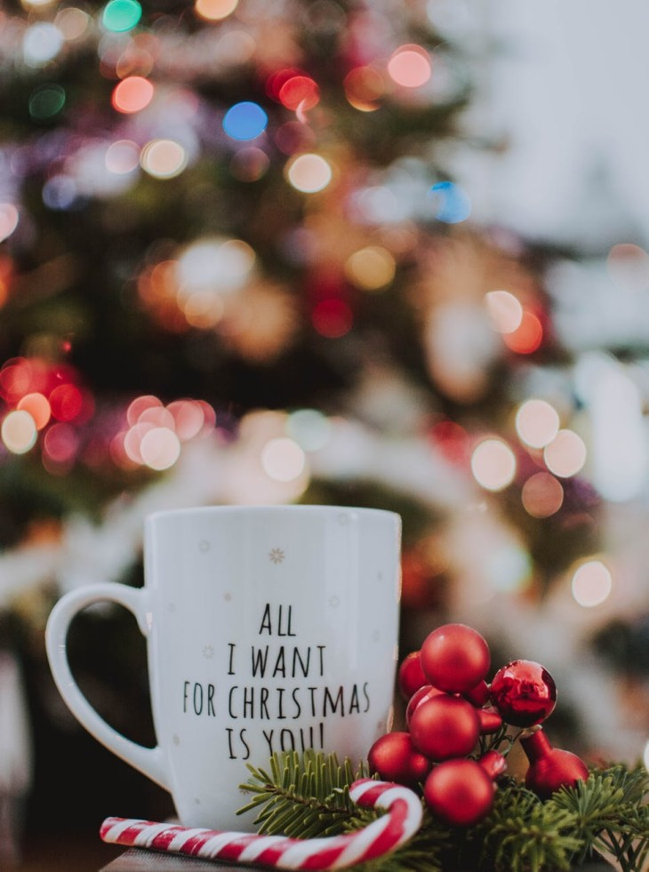 """A white mug that says """"all I want for Christmas is you""""  on it filled with hot Choi late and marshmallows. In front of a blurry Christmas tree."""