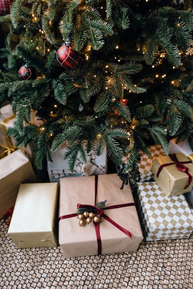 A Christmas tree with presents underneath- a  close up
