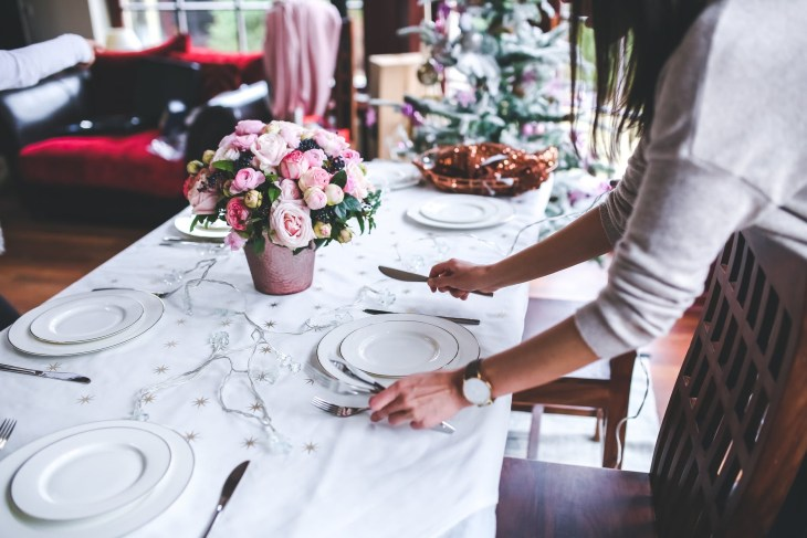 A kitchen table with pink flowers in the middle and someone setting up plates and cutlery for a dinner , all white themed.