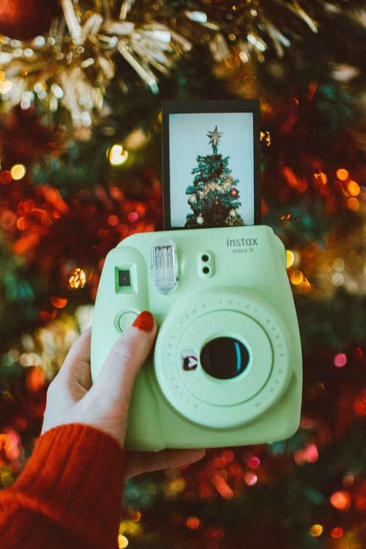 A green/blue Instax Mini Camera facing towards the camera with a Christmas tree picture printing out of the top of the camera.
