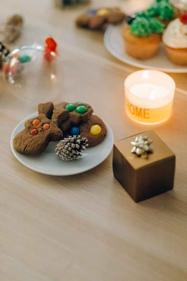 """A selection of Christmas biscuits on a white plate with a pine cone that is frosted, next to a gold Christmas present box with a bow and a candle with the words """"home"""" on it."""