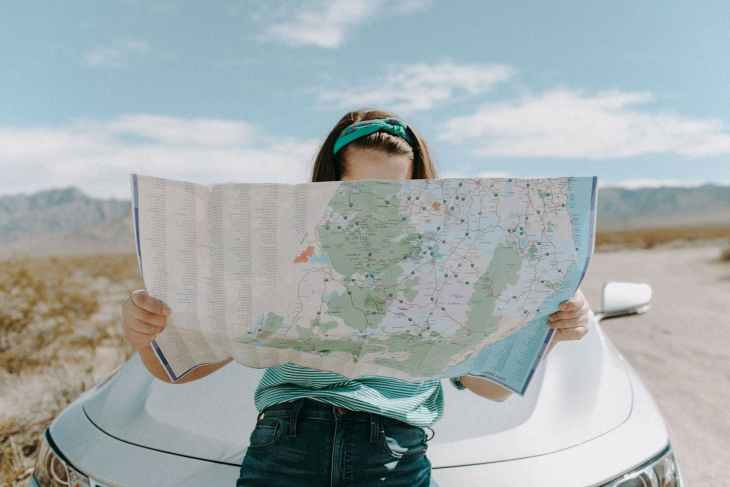 A girl sitting on a car bonnet holding out a huge map whilst outside in the middle of nowhere.