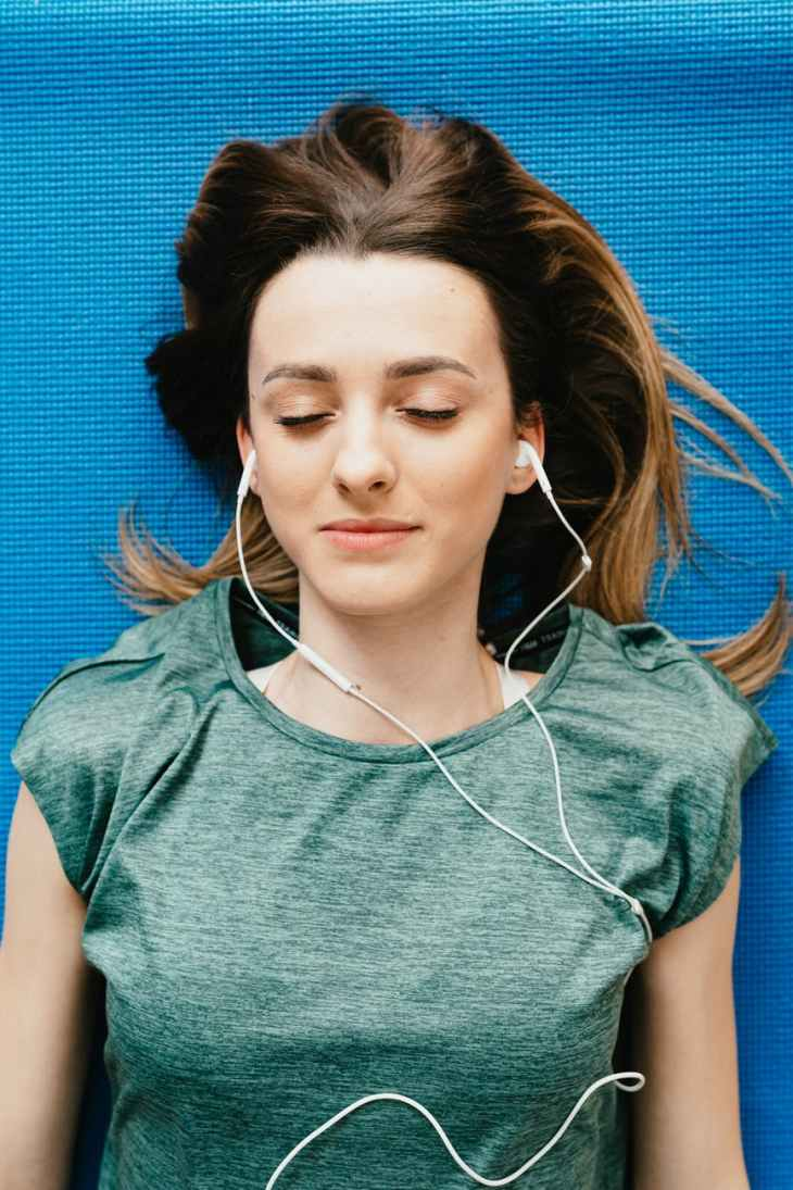 A woman laying down on the floor with her eyes closed and her ear phones in. practicing self-love.