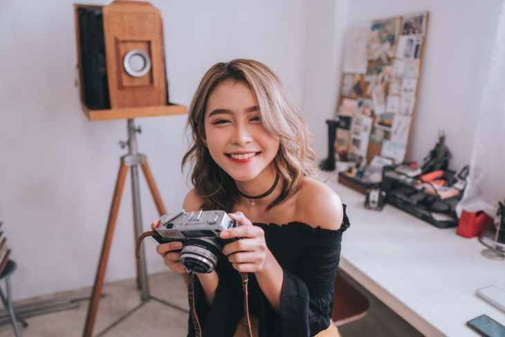 A woman holding a camera to the floor whilst smiling at the camera taking the picture of her. Sitting on a chair in front of a desk which is not as focused.