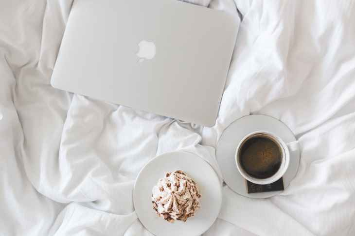 A white bed sheet with a white apple laptop, a coffee in a cup and saucer and a hot chocolate with cream and chocolate dust on a saucer all on the bed.