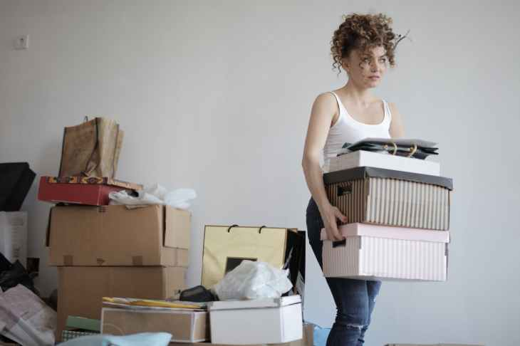 concentrated woman carrying stack of cardboard boxes for relocation. A small action to improve your life.