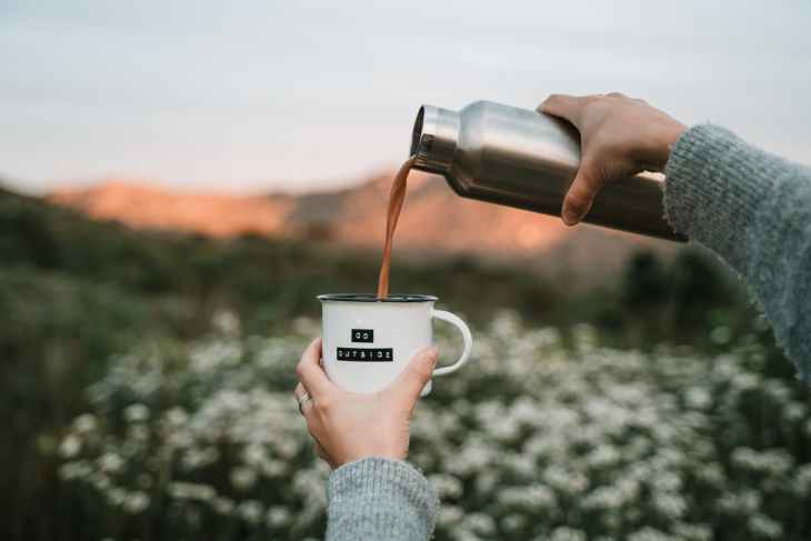 """A cup that says """"go outside"""" on it whilst a flask is pouring tea into it. With a blurry countryside background."""