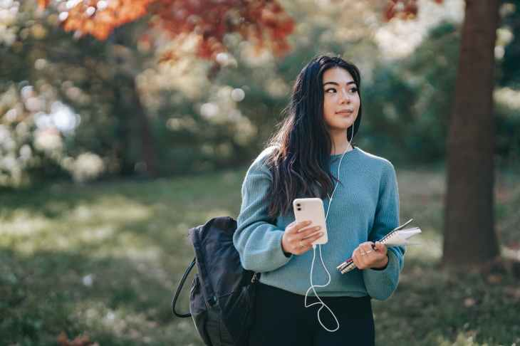 asian woman in earphones with notebook using smartphone in park taking