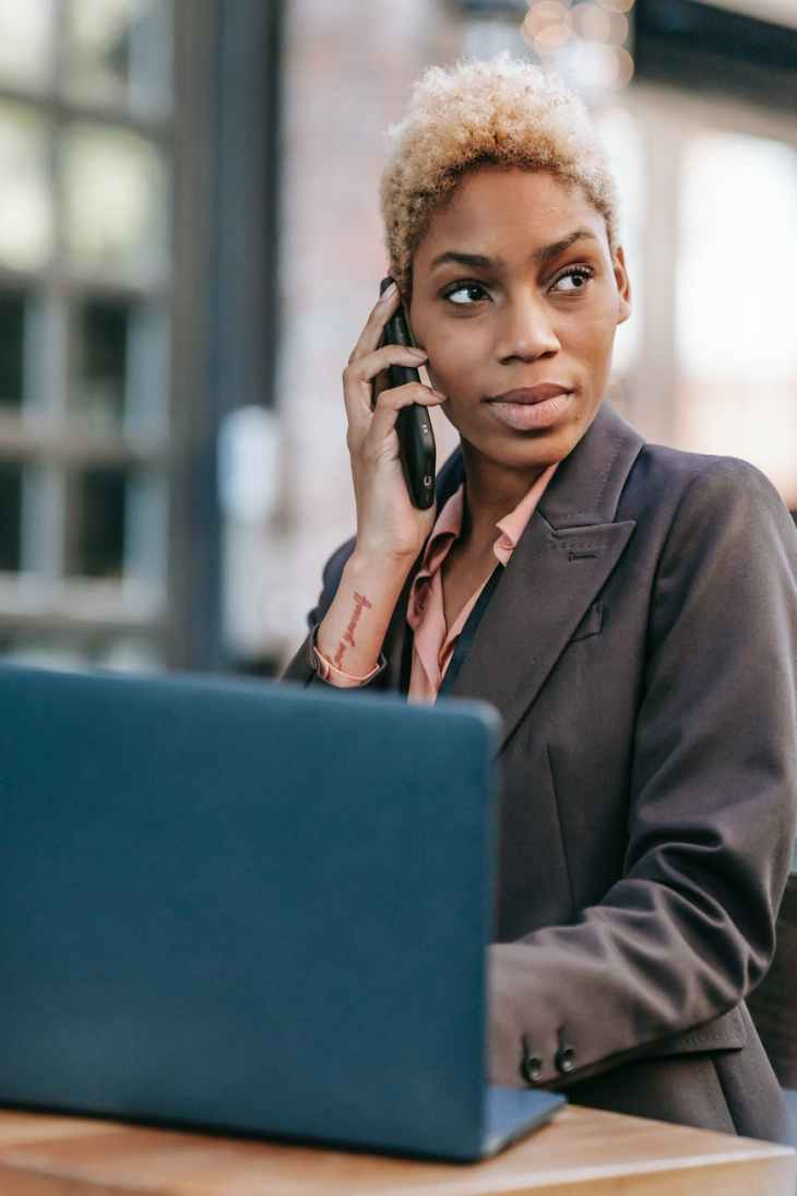 A woman on the phone looking to her left, dressed up smart in a suit whilst on her laptop on a table inside a building.