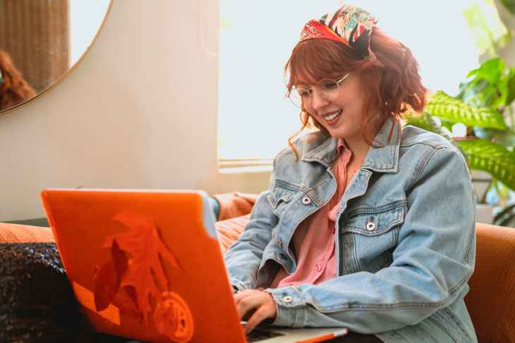 woman in denim jacket smiling while using her laptop