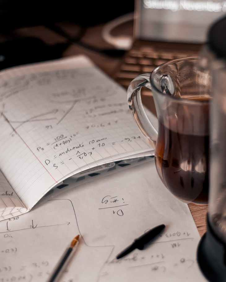 wood dawn coffee cup. Plus what to remember during exam results. Revising and notes on paper.