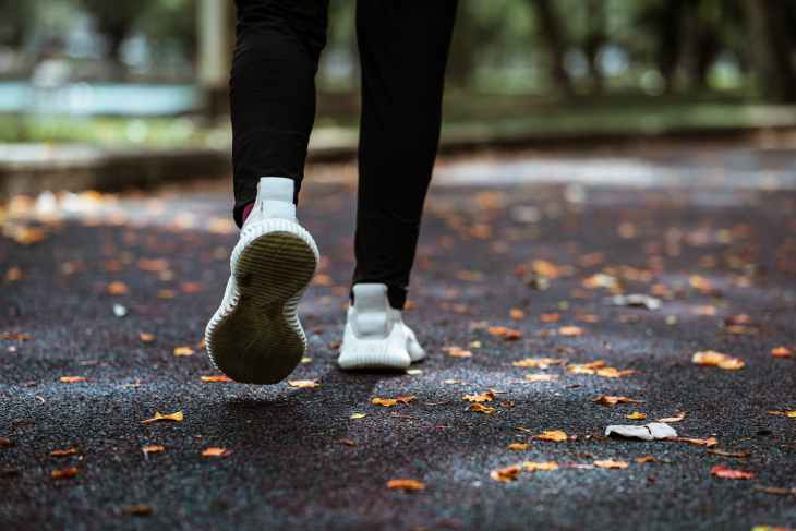 faceless person jogging in empty park doing fall workouts