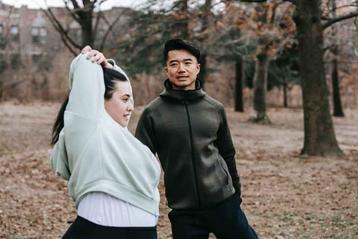 plus sized female training with asian man in park