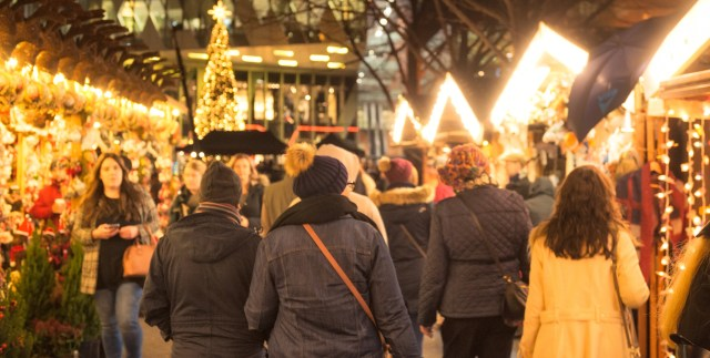 People browsing Christmas markets in Manchester at night
