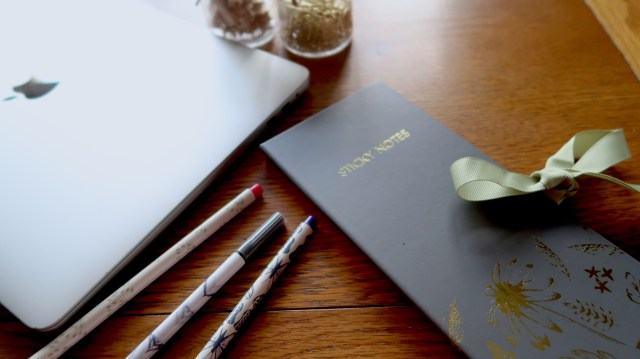 Pens, laptop and note book on wooden table