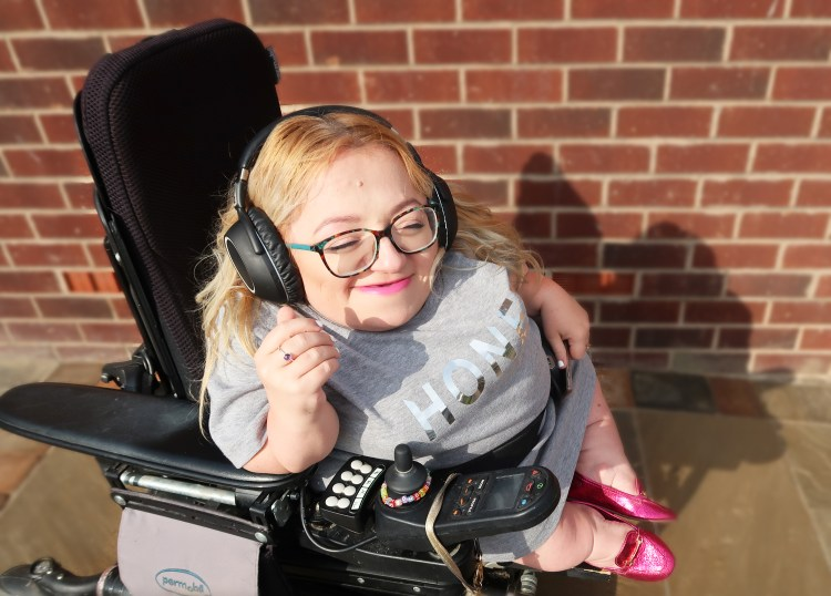 image of gem in wheelchair smiling with headphones on