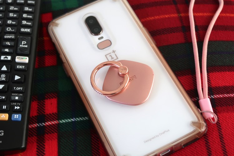 Image of back of white phone on tartan fabric with TV remote on the left of image
