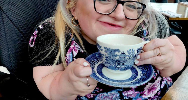 Gem Turner wearing purple floral dress holding blue china mug and plate