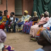 A group of women in colorful clothing and head scarves sit in a circle outdoors at a community meeting in Guinea-Bissau