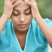 Image of Hispanic female nurse in blue scrubs holding her head in exhaustion with eyes closed