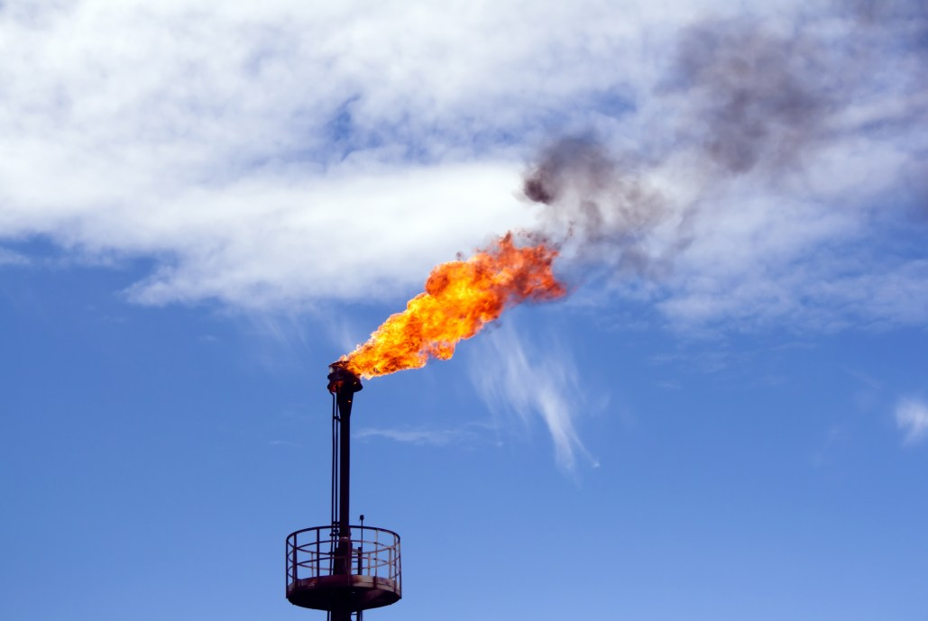 Gas flare from oil refinery smokestack against blue sky with clouds