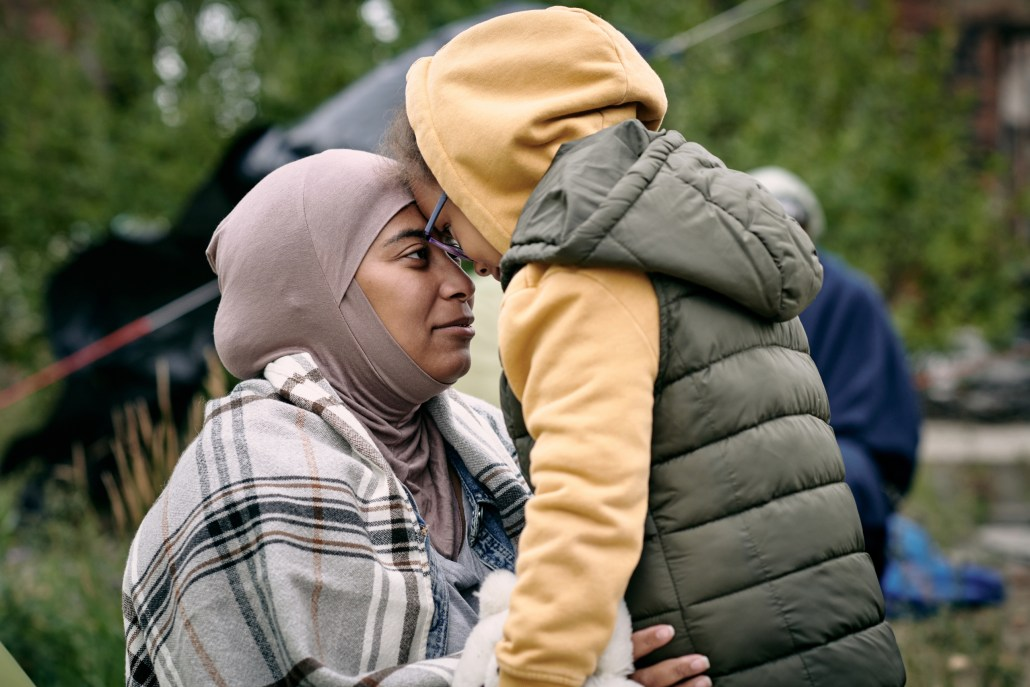 A refugee woman wearing a light purple headscarf and plaid wrap touches foreheads with her child, who is wearing a yellow hooded sweatshirt and green vest.