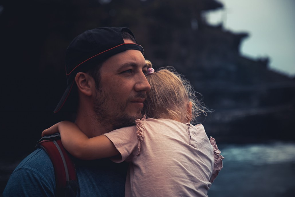 Pensive lonely man father holding his child daughter looking with hope into distance in dark vintage style