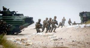 """US-amerikanische Nato-Soldaten laufen am 16.06.2016 in Ustka in Polen bei dem Marinemanöver """"Baltops"""" über einen Strandabschnitt vor Amphibienpanzern. An der Übung haben 17 Länder mit 6100 Soldaten teilgenommen. Foto: Kay Nietfeld/dpa (zu dpa-Story: """"Kalter Krieg in Europa? - Ein Reisebericht"""" vom 30.06.2016) +++(c) dpa - Bildfunk+++"""