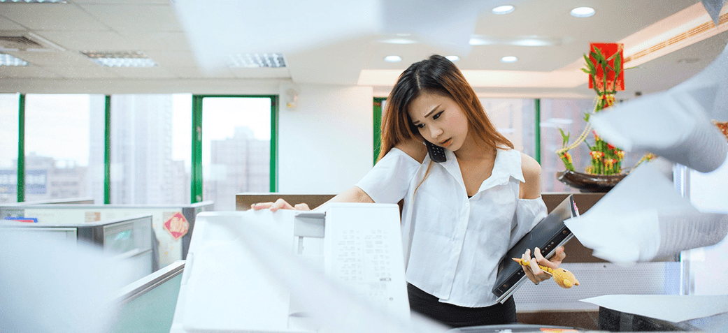 Woman at a copy machine with papers flying around her - internship advice