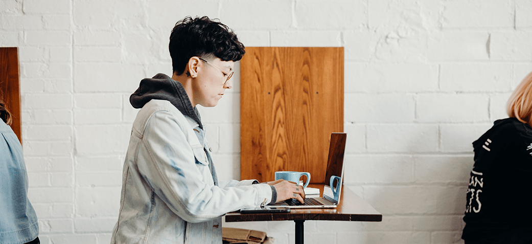 A person in a cafe on their laptop to find freelance work