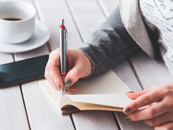 A woman writing successful pitches into a notebook