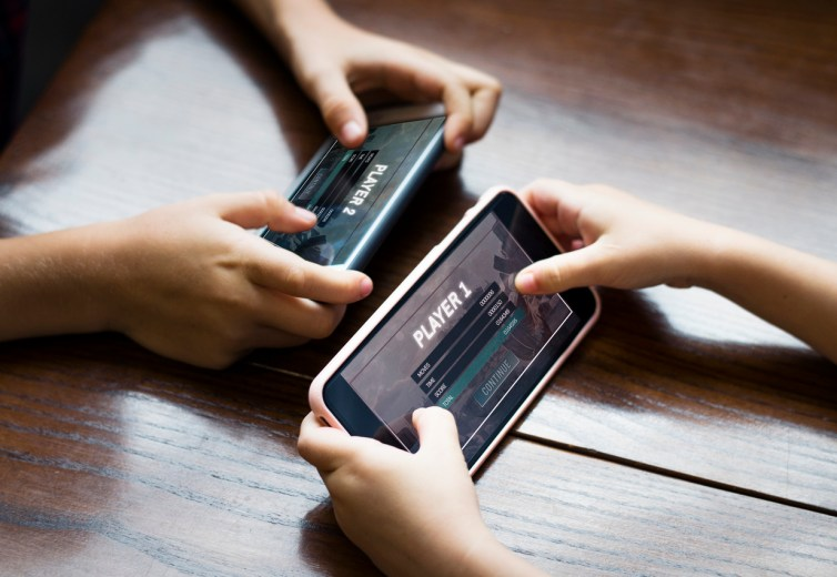 Two people playing games on their mobile phones at a table. Only their hands are in view.