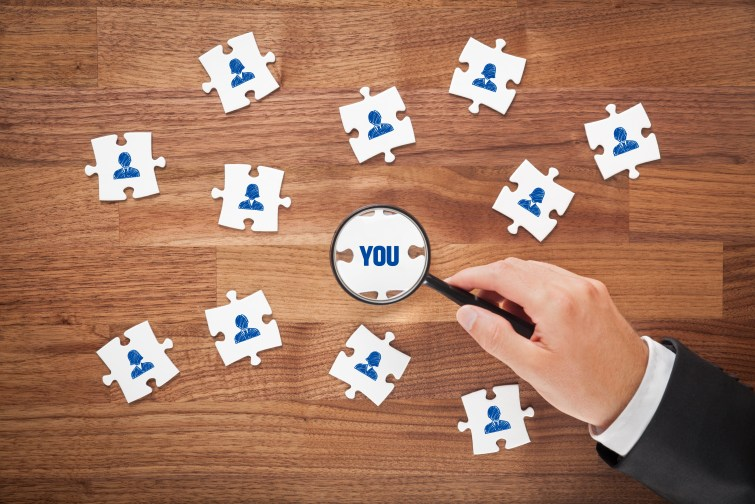 Magnifying glass focusing in on jigsaw puzzle piece marked 'you'