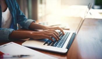 Close up shot of a woman using a laptop.